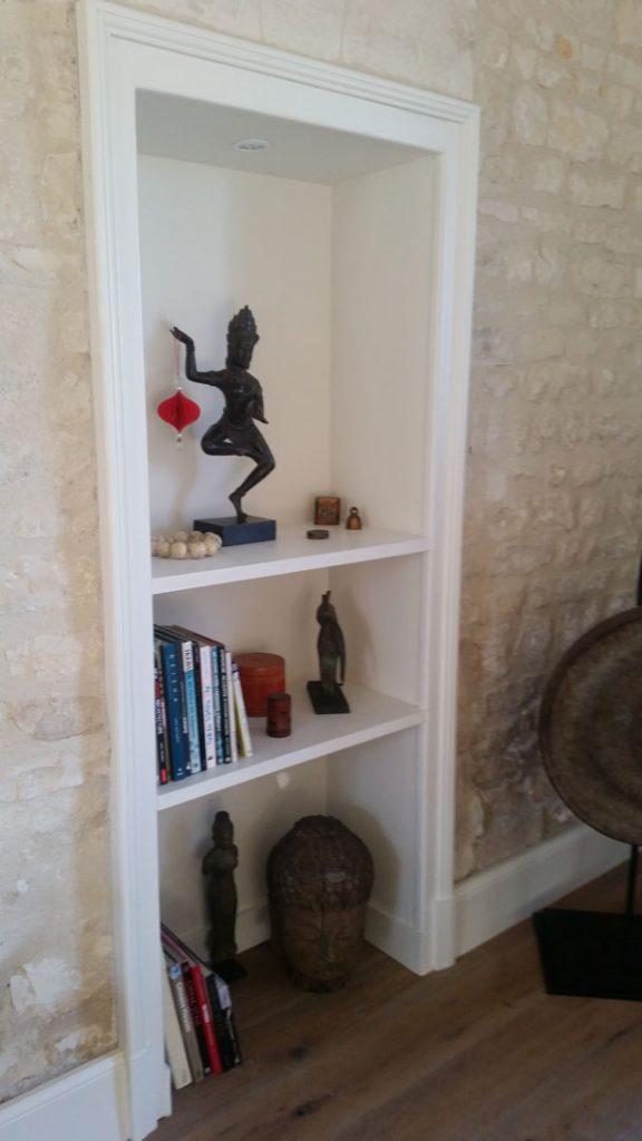 étagères en niche dans le mur en pierres