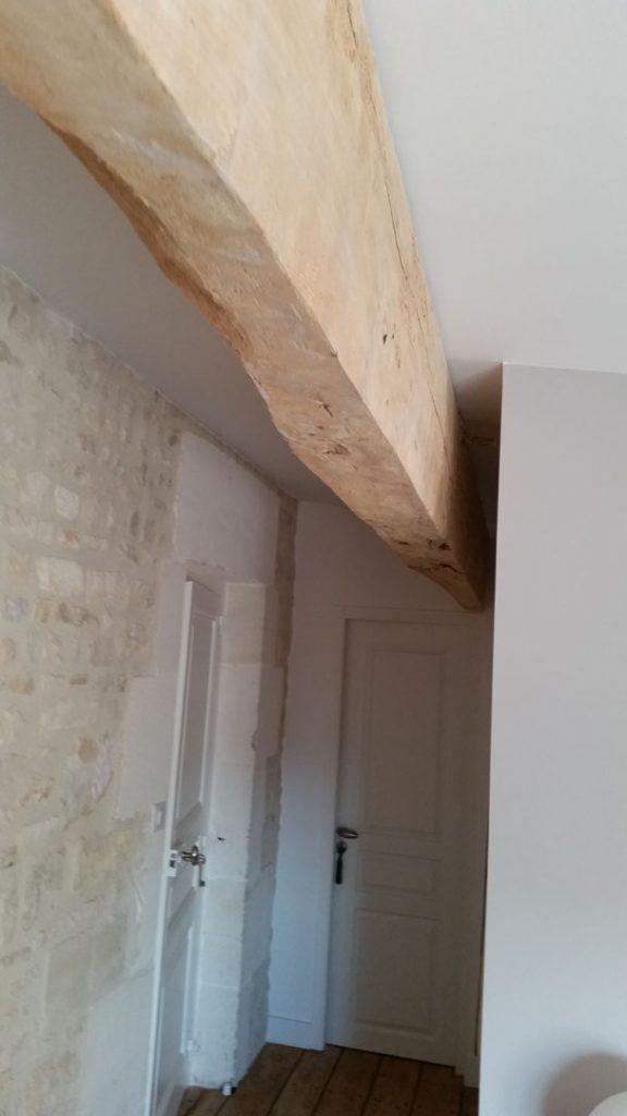 poutre au plafond et pierres au mur dans la maison