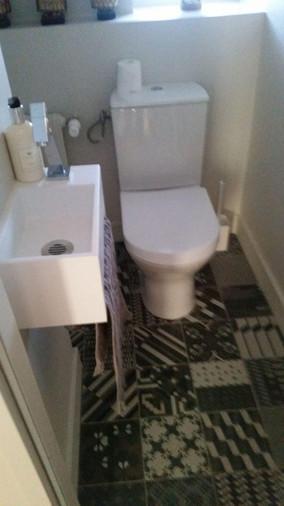 WC avec lave main et carrelage au sol